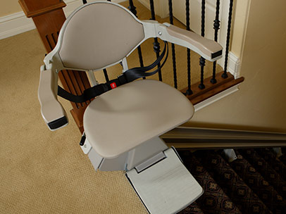 A newly installed stair lift at the top of a stair case