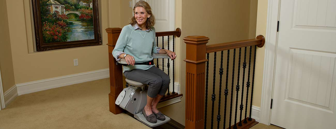 Woman happily ridding her new stair lift
