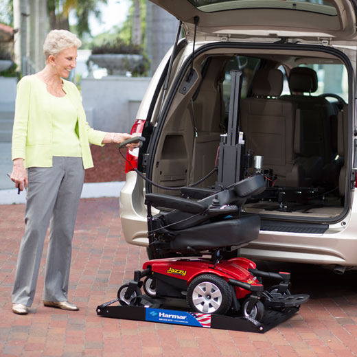 Woman loading up her power chair with a scooter lift.