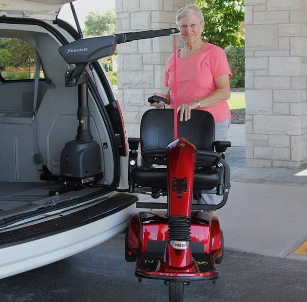 Woman using the curbsider mobility scooter lift.